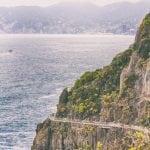 Cinque Terre- via dell'Amore w remoncie, ścieżka miłości, widac zbocze, na którym przeprowadzany jest remont ścieżki, skały porośnięte są żółtymi kwiatami, a w tle widac morze i zachmurzone niebo