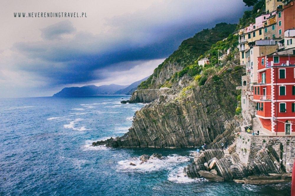 czerwone budynki w Cinque Terre, Riomaggiore na dole wzburzone morze i pochmurne niebo nad miastem