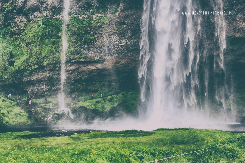 Seljalandsfoss wodospad na islandii z bliska ludzie chodzą za wodospad