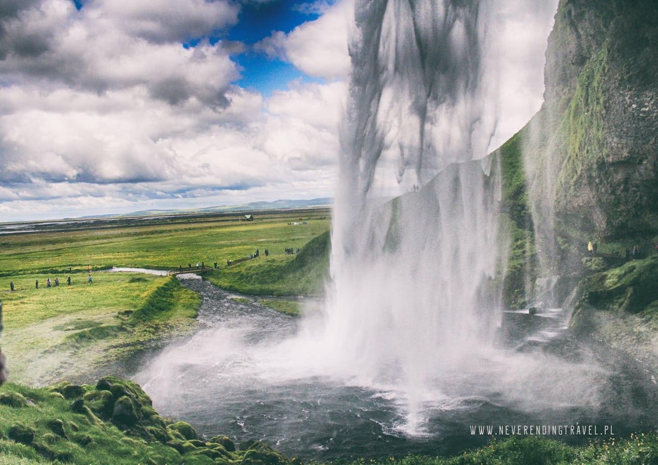 piękny, słynny wodospad na islandii Seljalandsfoss za który wchodzą ludzie, wejscie za wodospad, widok zza wodospadu