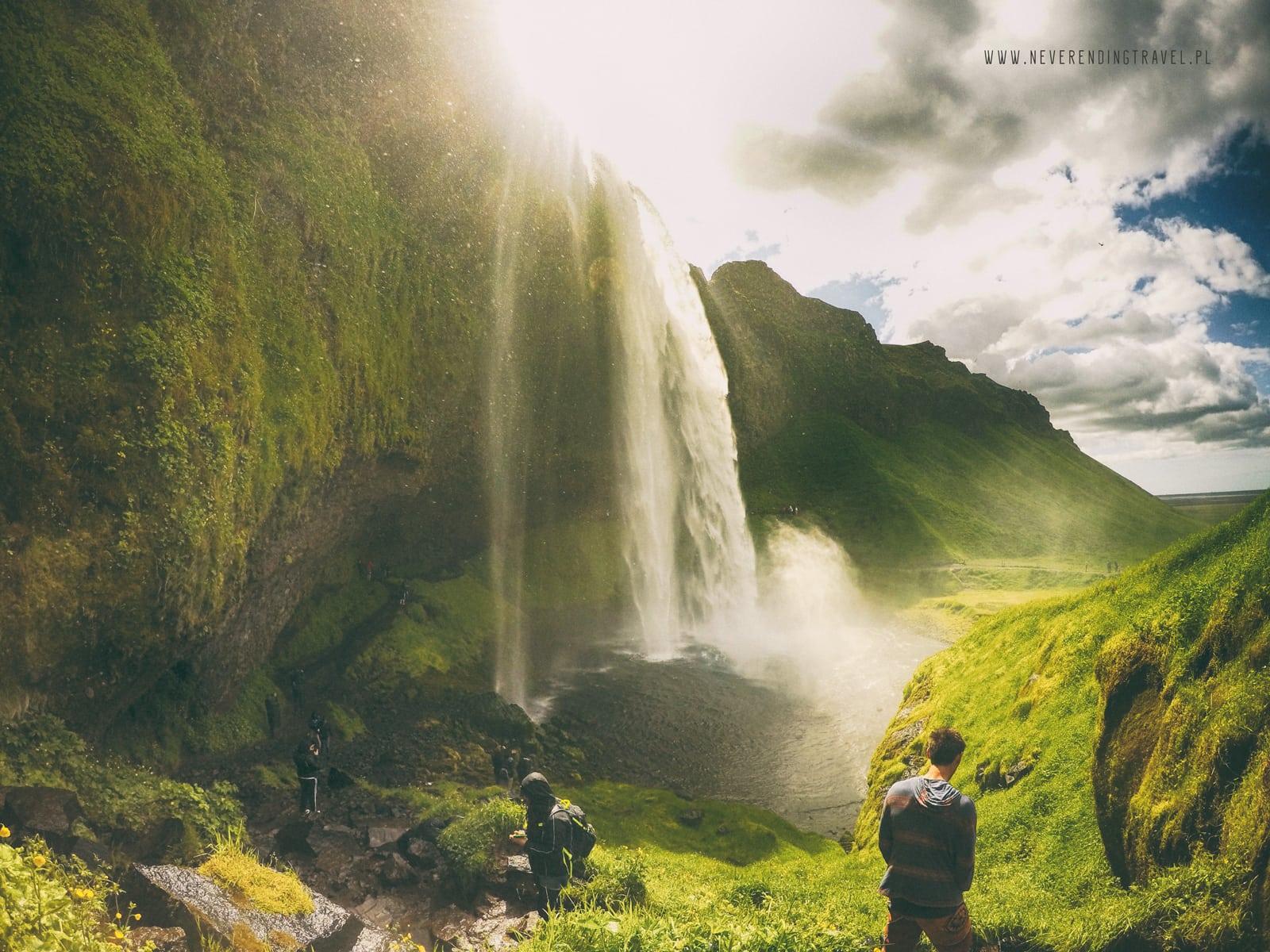 Seljalandsfoss islandzki wodospad neverendingtravel.pl widok wodospadu zza którego wyłania się słońce