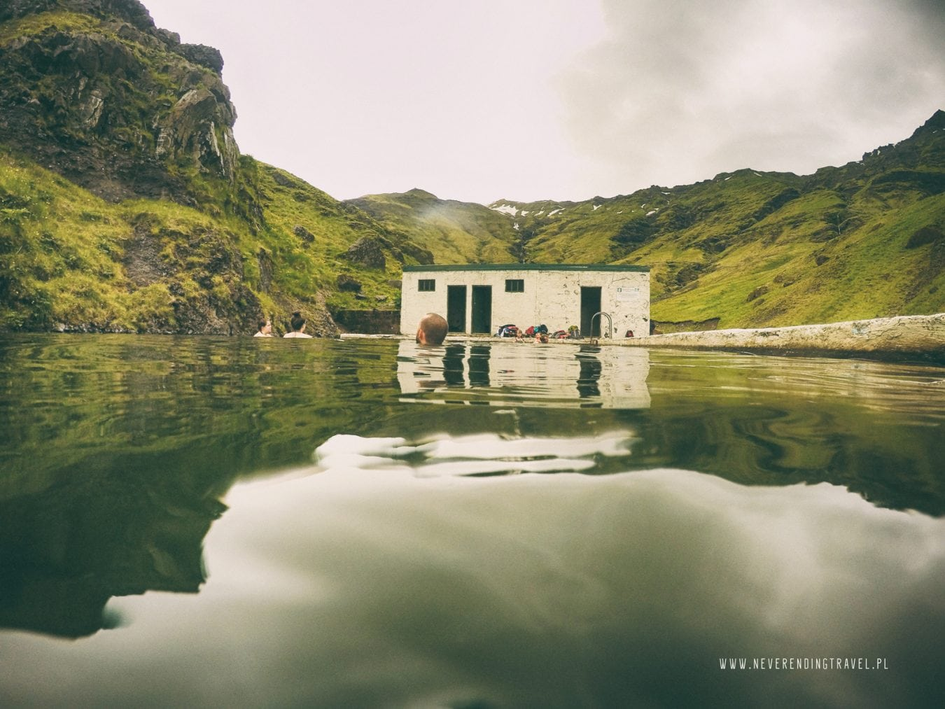widok z wody opuszczony basen Seljavallalaug w górach na Islandii neverendingtravel.pl