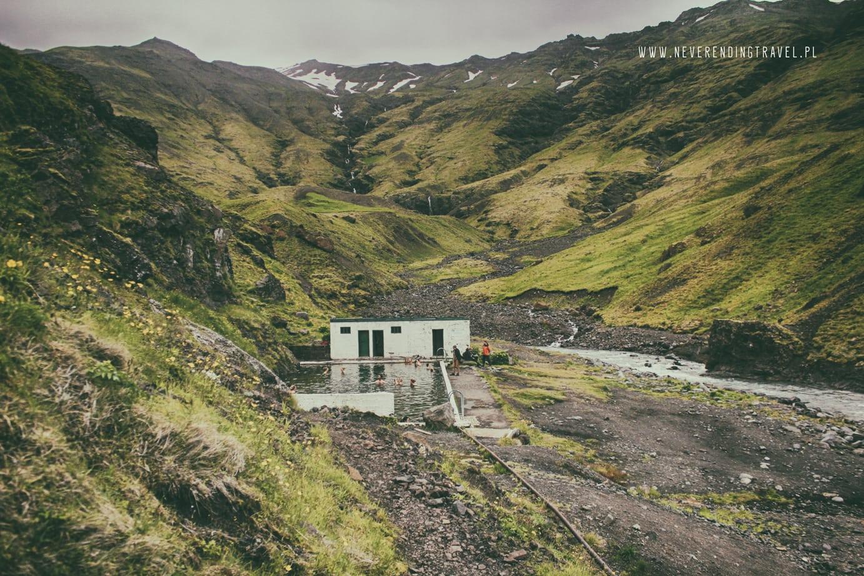 na pierwszym planie widac opuszczony basen Seljavallalaug z ciemną wodą, otoczony górami pokrytymi trawą
