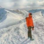 mezczyzna w tatrach ubrany w czerwoną kurtkę i raki idzie ośnieżoną granią zimą w stronę świnicy, jest słoneczny dzień w tatrach
