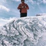 mężczyzna stoi na ośnieżonej skale w Tatrach, na nim niebieskie niebo,