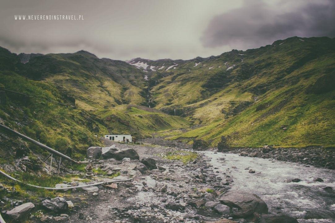 Seljavallalaug opuszczony basen na Islandii wśród zielonych gór widok ze ściezki wzdłuż rzeki, prowadzącej do basenu