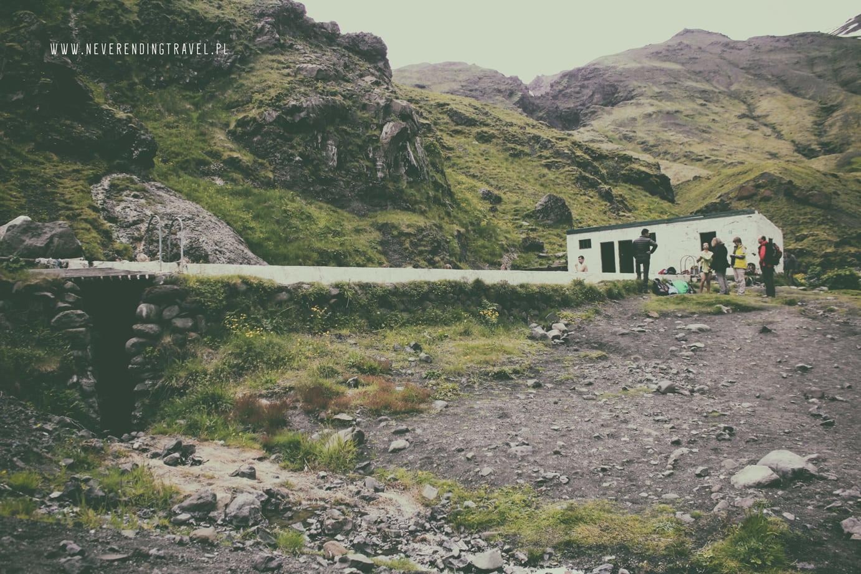 Seljavallalaug opuszczony basen na Islandii ludzie nad basenem i budynek przebieralni z tyłu sielone góry