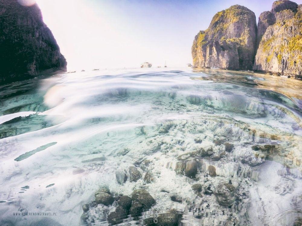 plaża maya bay na wyspie phi phi i krystaliczna woda, ujęcie nad samą taflą, widoczna rafa, w tle skały