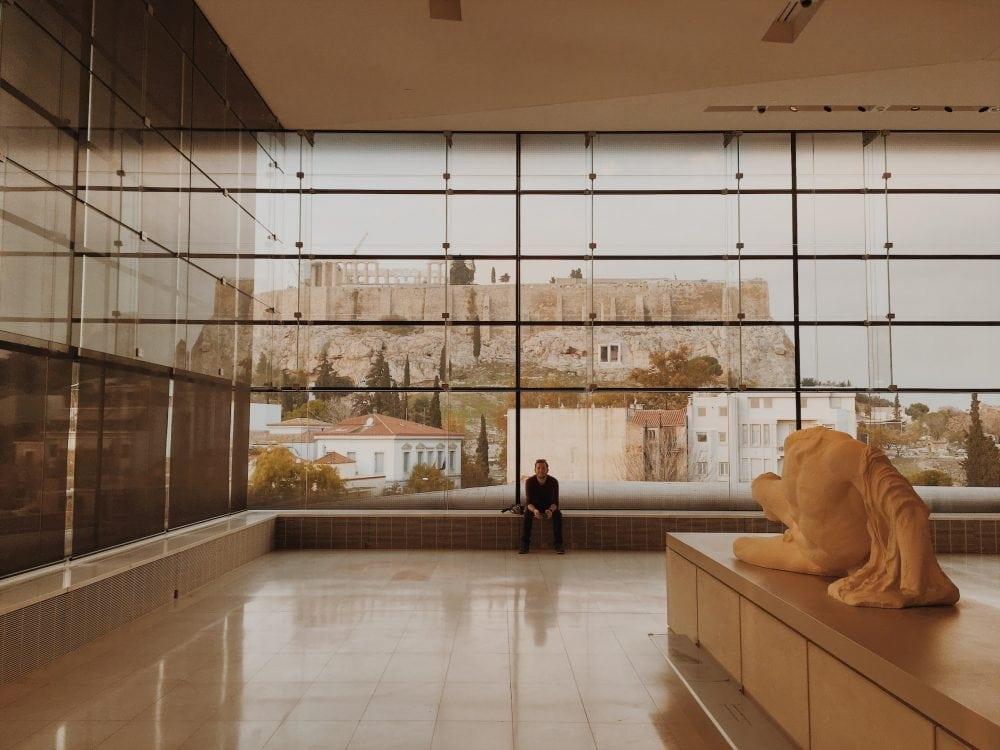 Jarek siedzi na parapecie pod oknem muzeum, a za nim jest przeszklona ściana i widok na akropol z nowego muzeum akropolu ateny neverendingtravel.pl