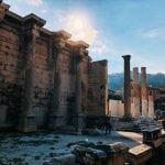 Ateny widok na ruiny za którymi wschodzi słońce, na pierwszym planie kolumny, za nimi ściana z marmuru neverendingtravel.pl Ateny na weekend