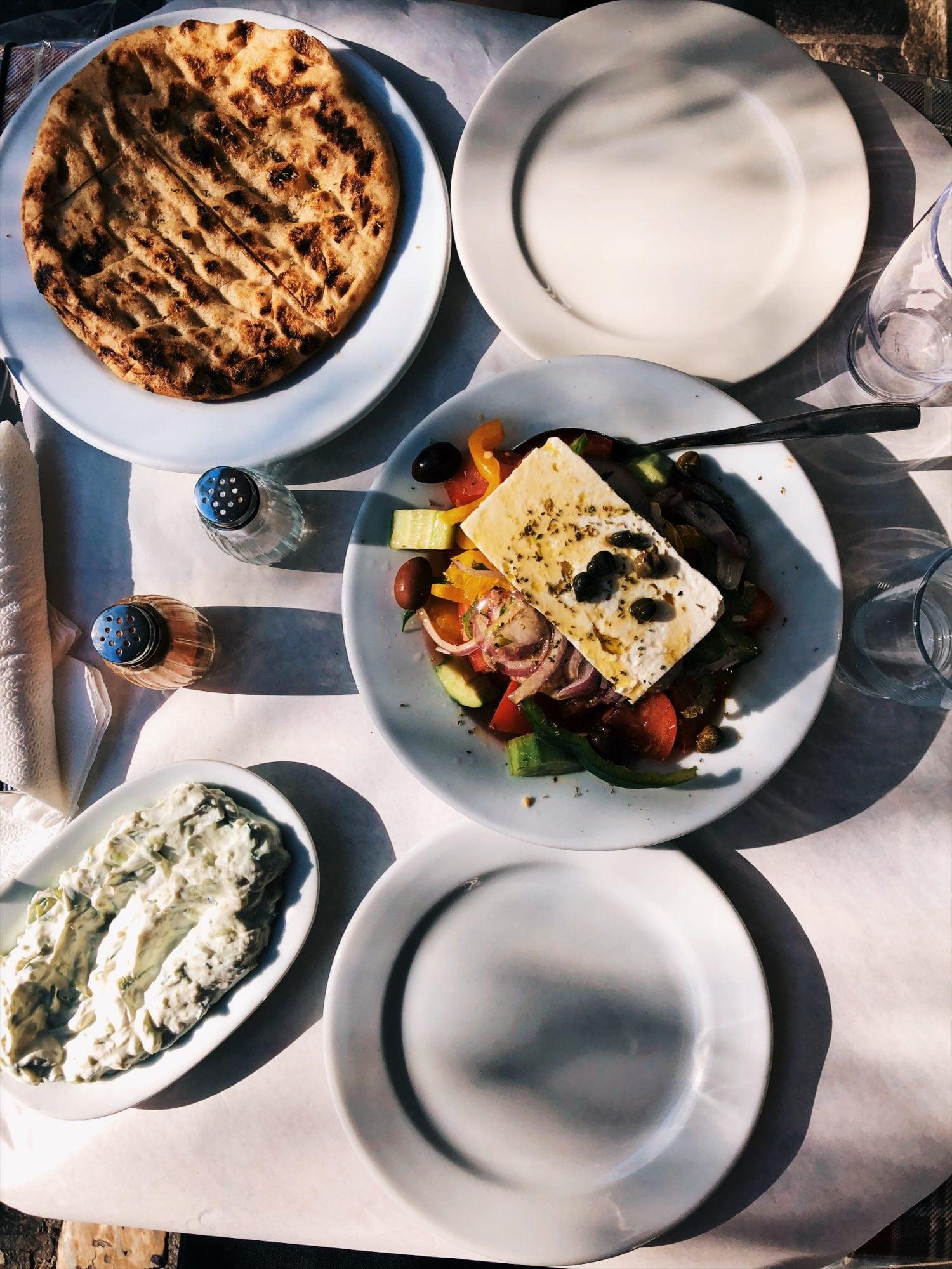lunch-w-Atenach-neverendingtravel.pl weekend w Atenach i nasza sałatka grecka oraz tzatzyki podane z pitą, zdjęcie zrobione z góry na stół z potrawami oraz naczyniami, zdjęcie zrobione słoneczny dzień