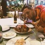 weekend w Atenach obiad w Atenach neverendingtravel.pl dużo mięsa na talerzu, tzatzyki oraz piwo, a nad tym pochyla się Jarek ubrany w pomarańczową kurtkę i otwierając szeroko oczy pokazuje jak jest głodny