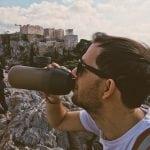 nasz weekend w Atenach, gdzie Jarek pije wode z bidona a w tle widać ruiny na Akropolu i ludzi neverendingtravel.pl