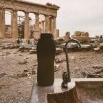 weekend w Atenach i nasz sposób na zapewnieni sobie dowy, bodon, stoi na kamiennym zlewie z którego wystaje kran, a w tle widać kolumny Partenonu, rusztowania i chodzących ludzi