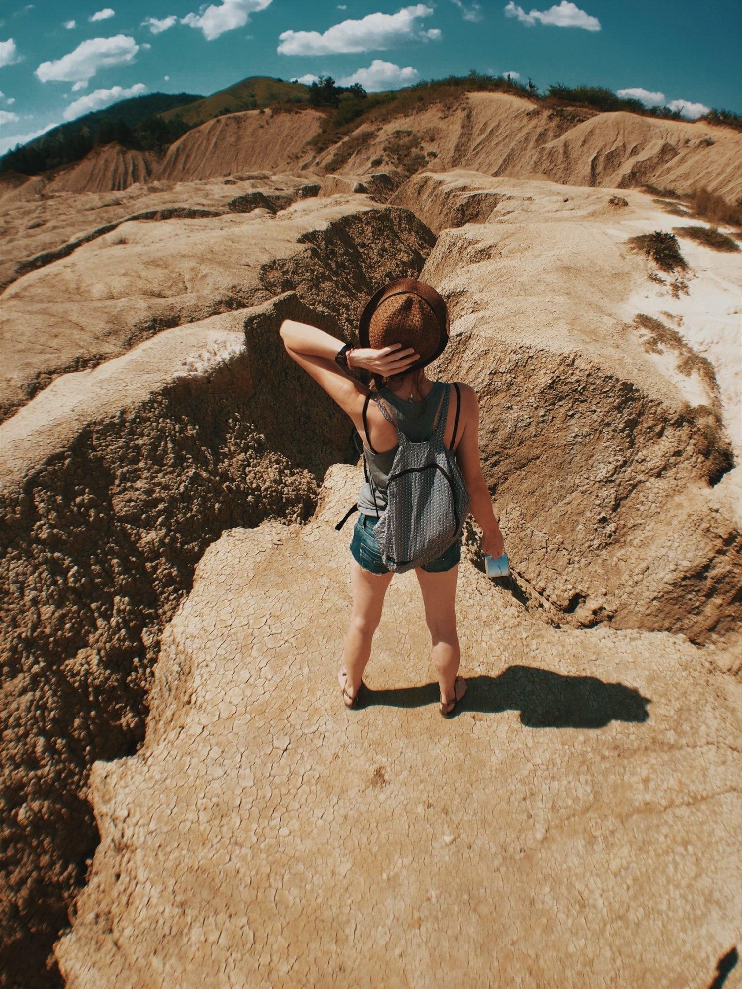 Aga stoi nad kraterem, kanionem, kobieta trzyma się za głowę, przytrzymując kapelusz od Medicine, w tle krajobraz wulkanów błotnych w Ruimunii buzau wulkany błotne rumunia neverendingtravel.pl