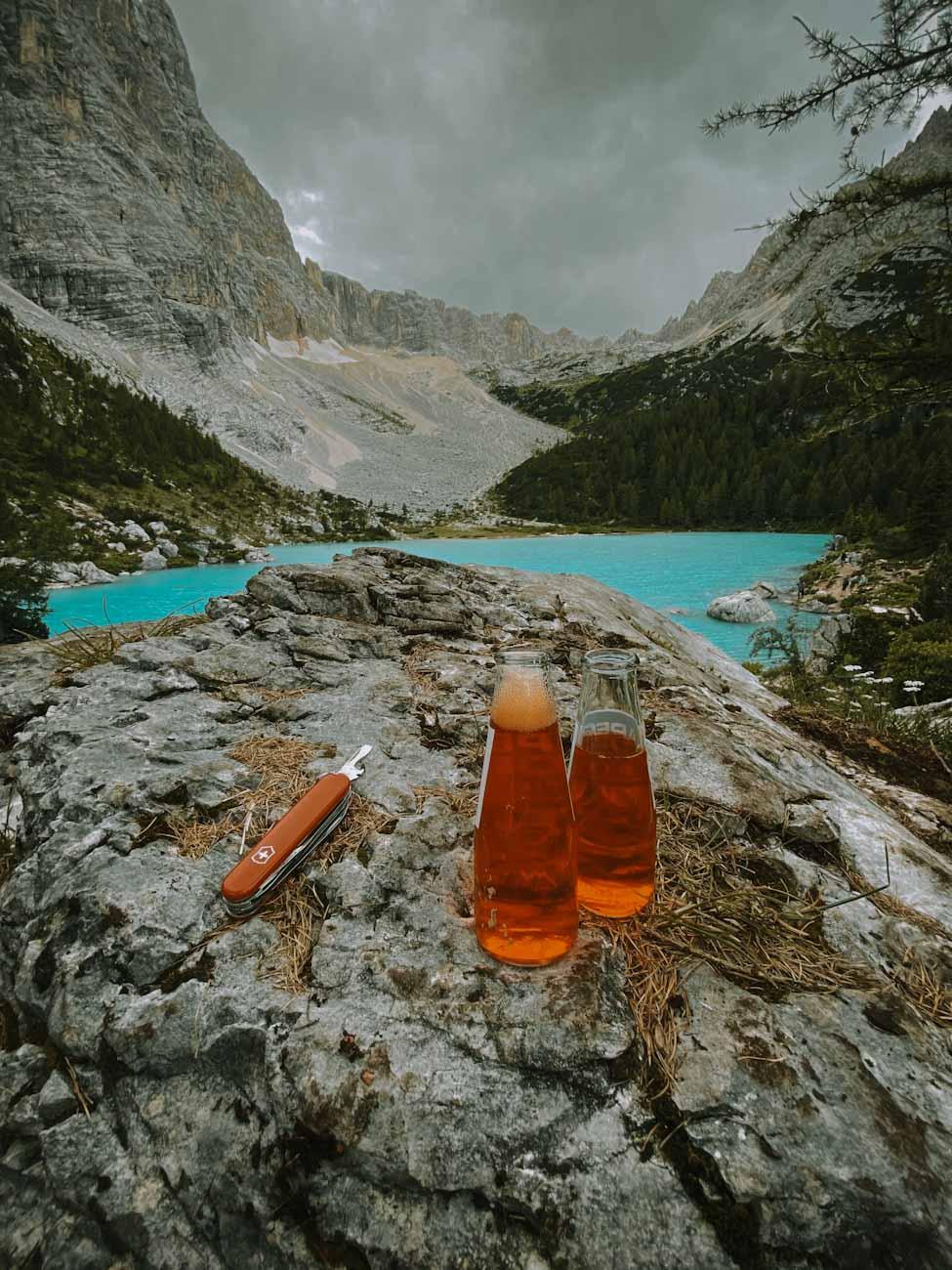 aperetivo nad Sorapis jeziorem w Dolomitach we włoszech, pomarańczowy drink w górach