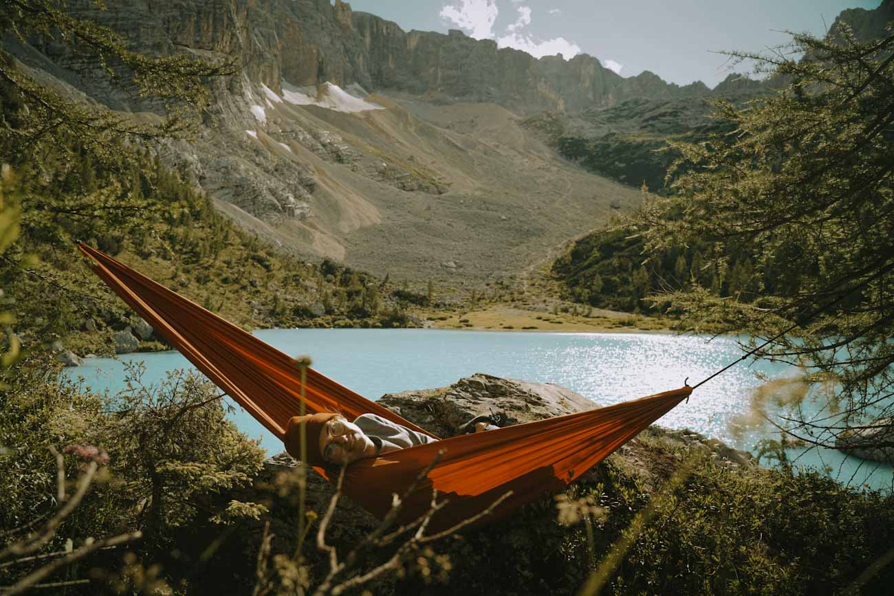 hamak nad jeziorem Lago di Sorapis najpiękniejsze jezioro w Alpach, Dolomity we Włoszech, góry, trekking we Włoszech, włoskie wakacje, turkusowe błękitne jezioro